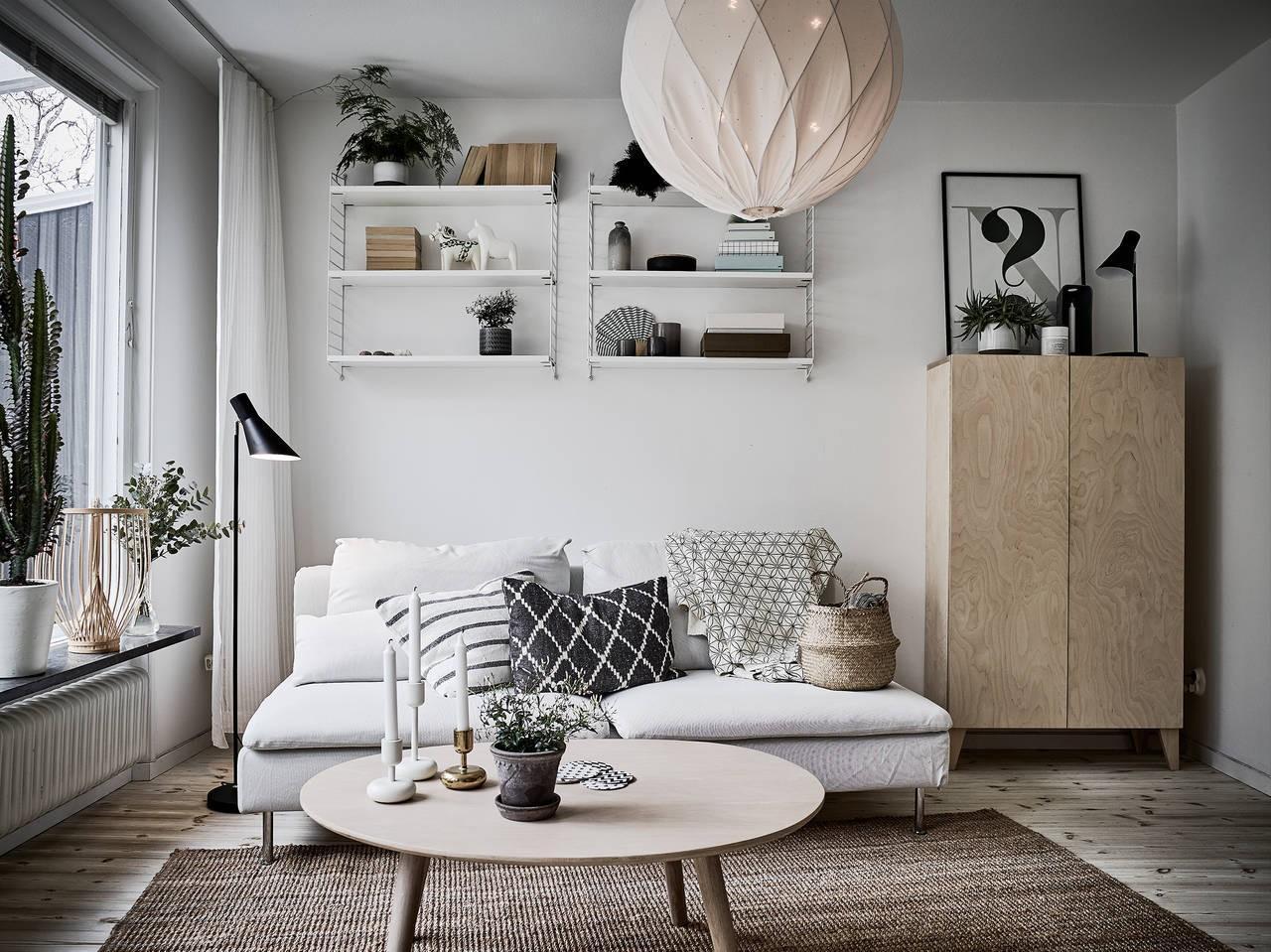 A skandináv stílusú nappali tele van világos színekkel, fával és gyakran kontrasztos fekete kiegészítőkkel.